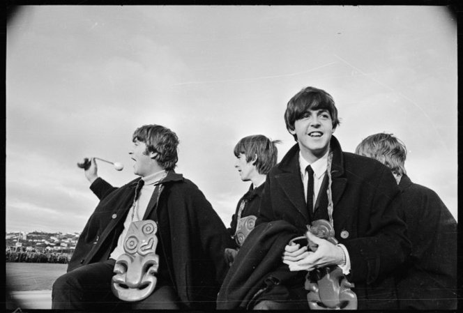 The Beatles at Wellington Airport, June 1964. They are wearing tikis (good-luck charms) around their necks. John is waving a poi, used by Maori female dancers.